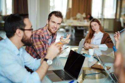 Profissionais em uma mesa de reunião discutindo sobre a visibilidade da empresa.